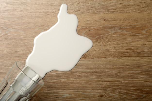 Plancher en bois avec verre de lait blanc renversé.