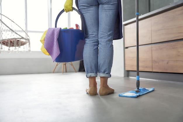 Plancher de lavage vue arrière d'une femme tenant une vadrouille et un seau ou un panier en plastique avec des chiffons
