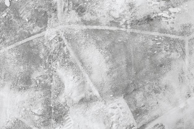 Plancher de mur de surface de dalle de béton gris avec neige et empreintes de pas à l'extérieur.