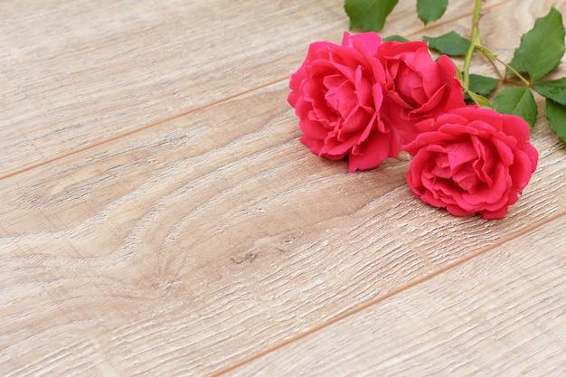Planches de bois avec de belles roses en arrière-plan. concept de donner un cadeau en vacances. vue de dessus.