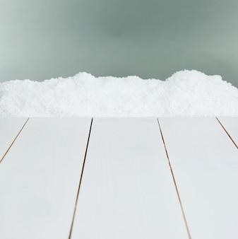 Planches de bois blanc avec de la neige sur fond gris