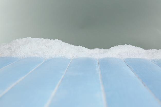 Planches de bois bleu avec de la neige sur fond gris
