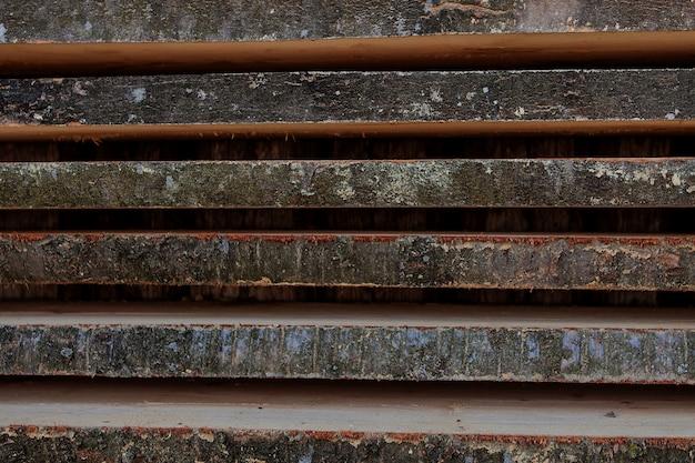 Planches en bois brun et gris pliées dans une scierie. planches d'aulne empilées comme fond de texture