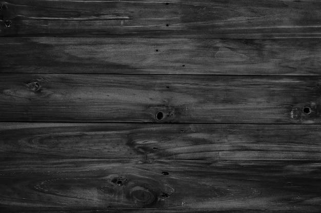 Planches de bois noir grunge rustique a souligné la texture de fond closeup