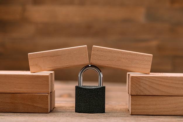Des planches de bois sont tombées sur un verrou suspendu fiable en tant que concept de sécurité financière, de risque, d'aide