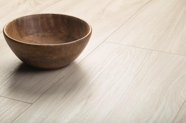 Planches en bois stratifié et parquet avec bol en bois