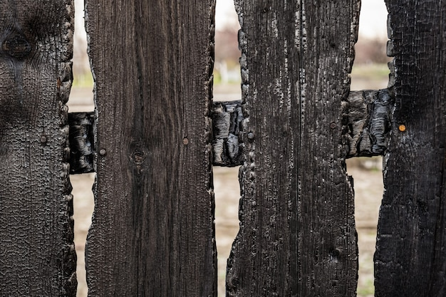 Des planches de clôture brûlées après un incendie dans une maison privée. conséquences d'une gestion non prudente et irréfléchie du feu.