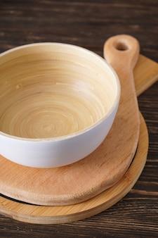Planches à découper en bois et un bol sur un fond en bois, vue du dessus.