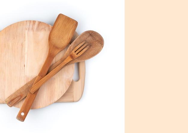 Planches à découper et spatules en bois sur fond blanc avec espace pour copier.