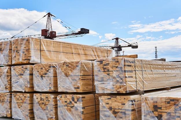 Des planches et des grues fraîchement emballées en arrière-plan dans la cour de la production de menuiserie