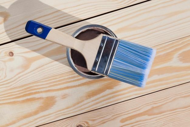 Des planches de pin blanchies prêtes à être peintes de couleur marron, un pinceau à poils bleus et une boîte de peinture sur la surface, un pinceau se trouve sur le pot