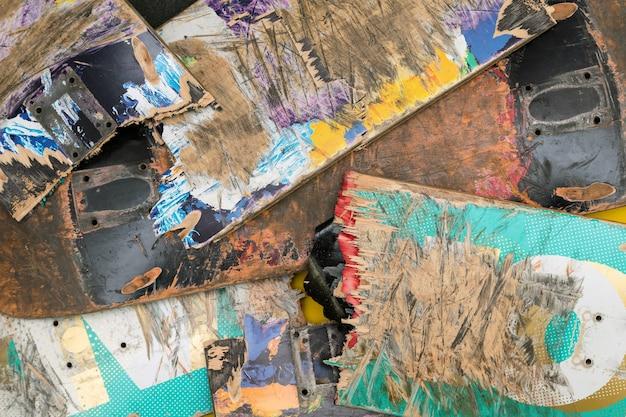 Des planches de skateboard colorées cassées empilées les unes sur les autres.