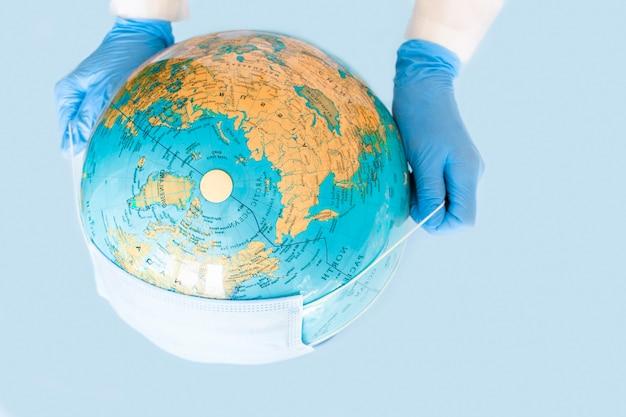 Planète terre dans un masque médical de protection bleu isolé concept minimal épidémie de virus corona covid écologie de protection de la terre