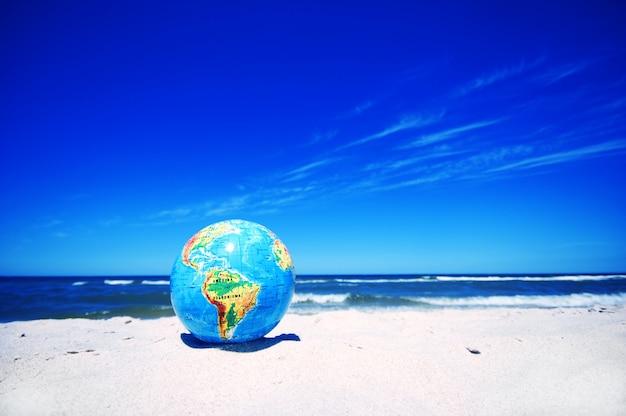 Planète terre sur la plage de sable