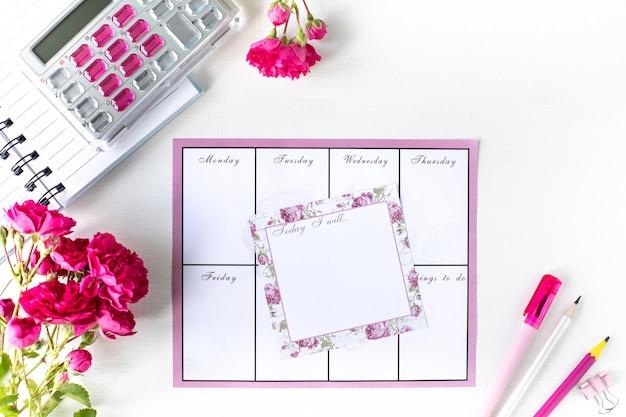 Planeur avec notes et liste de tâches sur fond blanc avec papeterie rose. concept d'entreprise