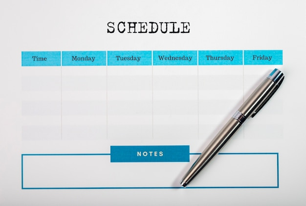 Planificateur hebdomadaire vide ou organisateur avec stylo, pose à plat.