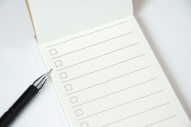 Planificateur de liste de tâches vide avec liste de contrôle et stylo noir sur fond blanc, gros plan