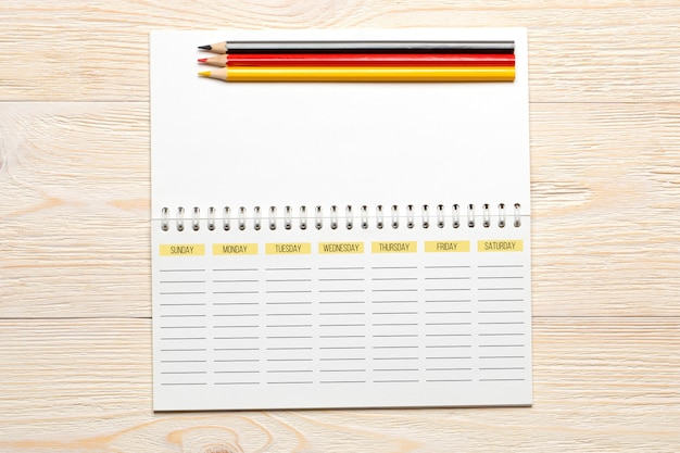 Planificateur de semaine vide avec des crayons sur tableau blanc, concept de lieu de travail