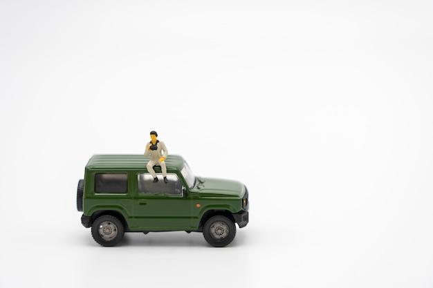 Planificateur de voyage permanent de personnes miniatures avec modèle de voiture de jouet verte