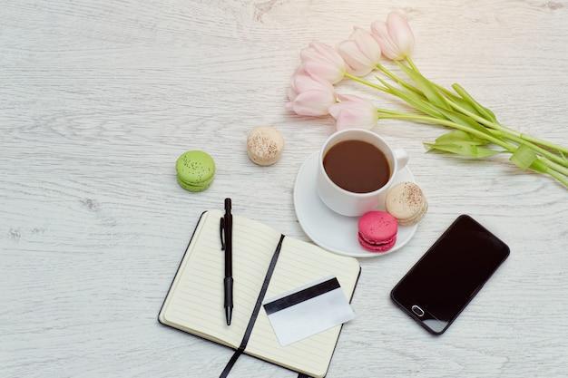 Planification des affaires. tasse à café avec dessert, cahier, stylo, carte de crédit et téléphone.