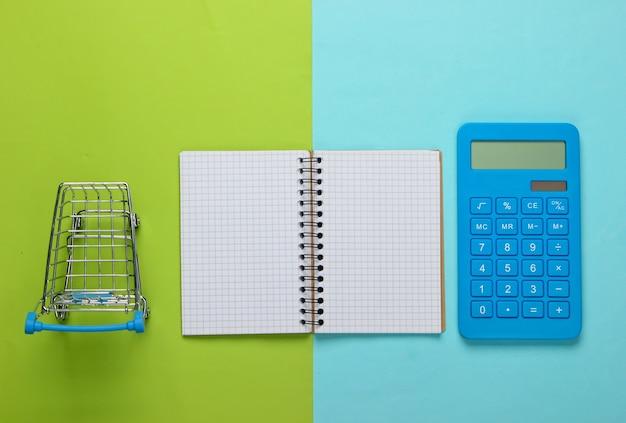 Planification et calcul des coûts d'achat. calculatrice avec bloc-notes et caddie de supermarché sur fond bleu vert. vue de dessus