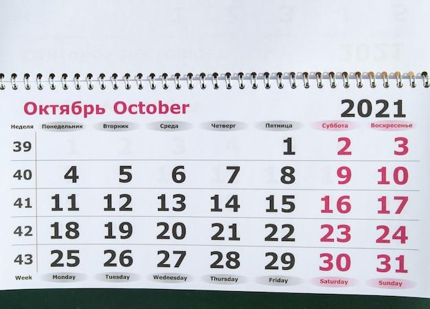 Planification d'un calendrier d'affaires pour le concept d'entreprise de mur de papier d'octobre 2021 avec texte anglais et russe