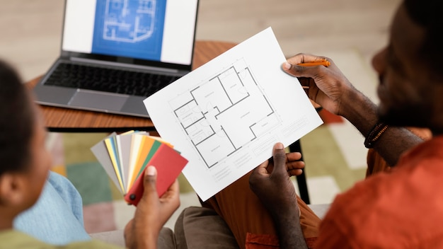 Planification de couple sur la maison de redécoration à l'aide d'un ordinateur portable et d'une palette de peinture