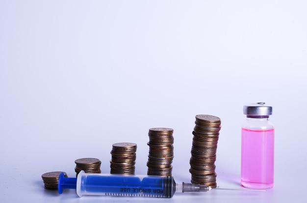 Planification financière, concept de croissance de l'argent. seringue médicale, flacon en verre avec liquide rose et piles de pièces dans l'ordre croissant. copier l'espace