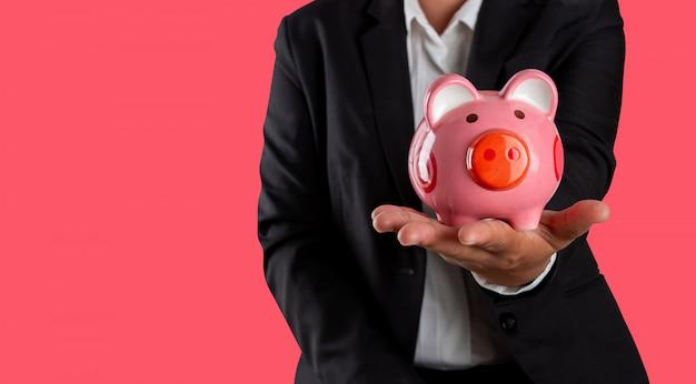 Planification financière, homme d'affaires détenant en tirelire en main isolé sur rose magenta.