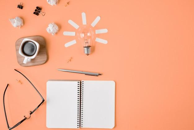 Planification financière laïque plat image de table malpropre en désordre avec un panneau d'agrafe vide, fournitures de bureau, stylo, bloc-notes, lunettes de vue, tasse de café, ampoule sur fond orange.