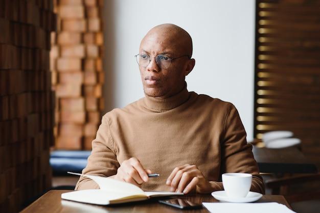 Planification de la journée. étudiant noir calme écrivant son horaire de cours dans un cahier, assis dans un bar moderne, espace vide
