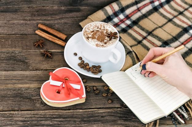 Planification matinale coupe de cappuccino, main féminine avec un crayon et un bloc-notes sur une table en bois marron