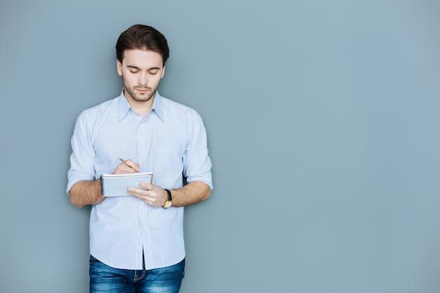 Planification quotidienne. sérieux bel homme intelligent debout sur fond gris et prendre des notes lors de la planification de sa journée