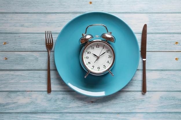 Planification des repas pour le concept de régime, concept de jeûne intermittent avec horloge sur plaque, fourchette et couteau sur table en bois