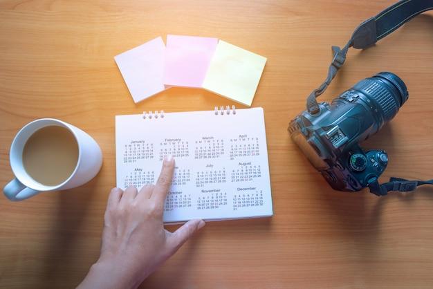 Planification de voyage sur le calendrier et utilisez post-it pour noter avec une tasse de café sur une table en bois