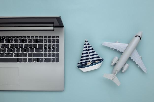 Planification de voyage. ordinateur portable et voilier, avion sur fond bleu. vue de dessus. mise à plat