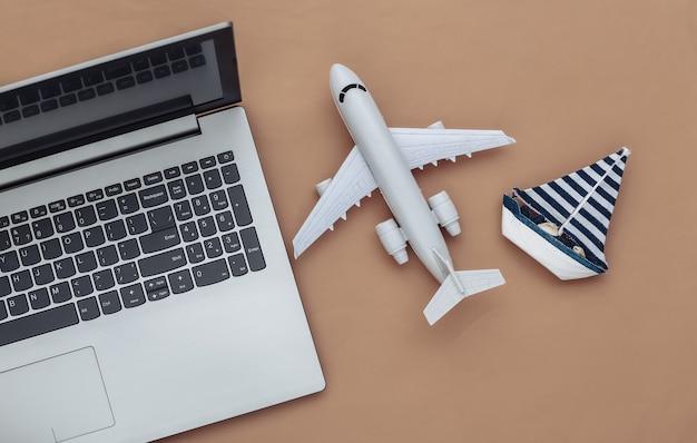 Planification de voyage. ordinateur portable et voilier, avion sur fond marron. vue de dessus. mise à plat