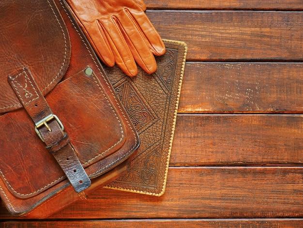 Planification de voyage porte-documents en cuir de vieux livre et gants sur fond de bois