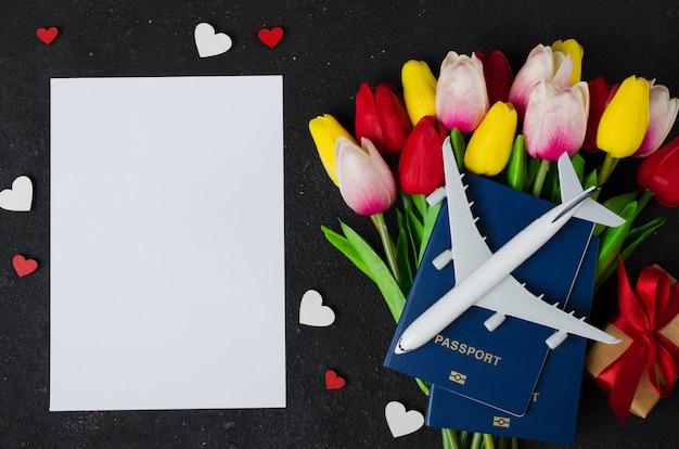 Planification de voyage de vacances. concept de voyage avec modèle d'avion, passeports, papier vierge, tulipes bouquet et boîte-cadeau.