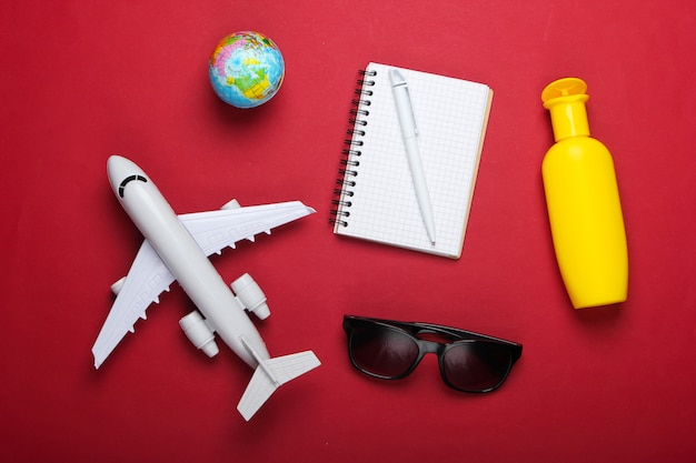 Planification des voyages et des vacances à la plage. fond d'été. figurine d'avion, globe, lunettes de soleil et écran solaire, ordinateur portable sur fond rouge. vue de dessus. mise à plat