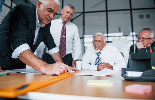 Planifier la construction en la mesurant sur papier. une équipe âgée d'architectes d'affaires âgés a une réunion au bureau.
