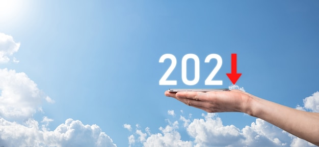 Planifier une croissance négative de l'entreprise dans le concept de l'année 2021. plan d'affaires et augmentation des indicateurs négatifs dans son entreprise, baisse des concepts commerciaux. maintenez la main sur fond de ciel.