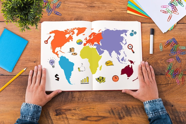 Planifier son voyage. vue de dessus image en gros plan d'un homme tenant la main sur son ordinateur portable avec une carte colorée dessus alors qu'il était assis au bureau en bois