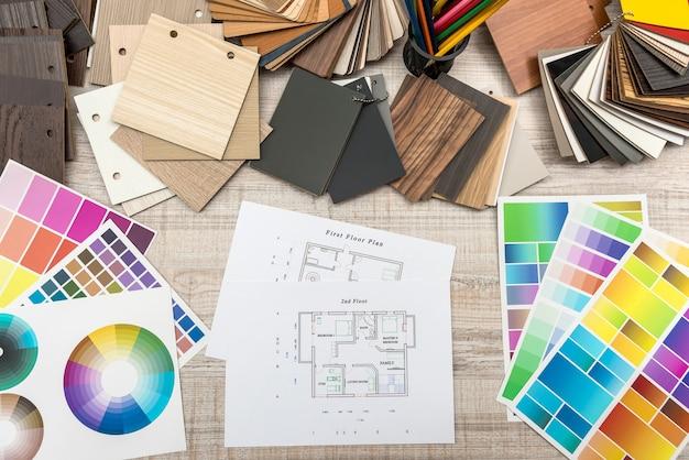 Plans architecturaux avec papier et échantillonneur de couleurs en bois sur un bureau créatif.