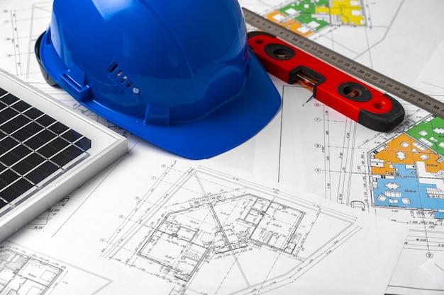 Plans de construction casque et batterie solaire sur la table des architectes
