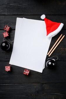 Plans de nouvel an papier vide et ensemble de décoration d'arbre de noël, vue de dessus à plat, avec espace de copie pour le texte, sur fond de table en bois noir