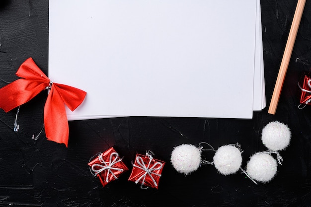 Plans de nouvel an papier vide et ensemble de décoration d'arbre de noël, vue de dessus à plat, avec espace de copie pour le texte, sur fond de table en pierre noire noire