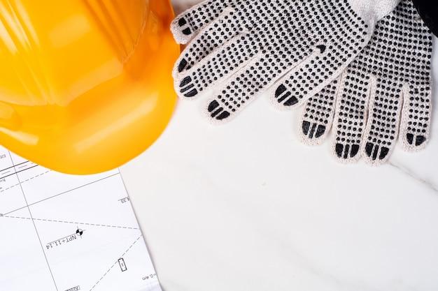 Plans, ruban à mesurer, gants et casque.