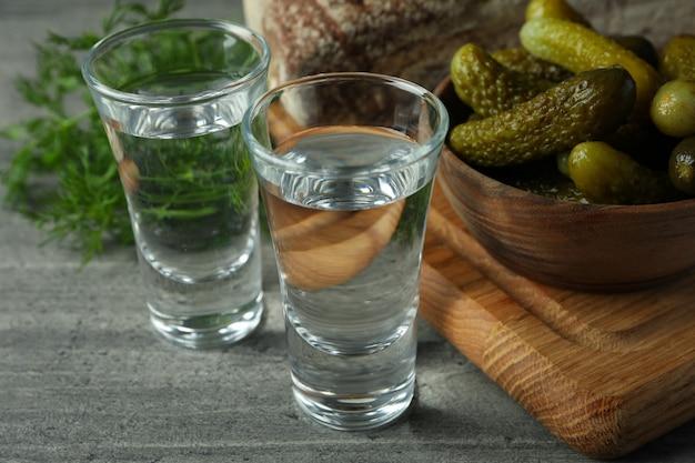 Plans de vodka, cornichons, pain et aneth sur table grise