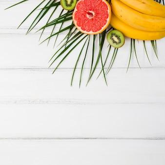 Plante feuilles près de fruits exotiques frais à bord